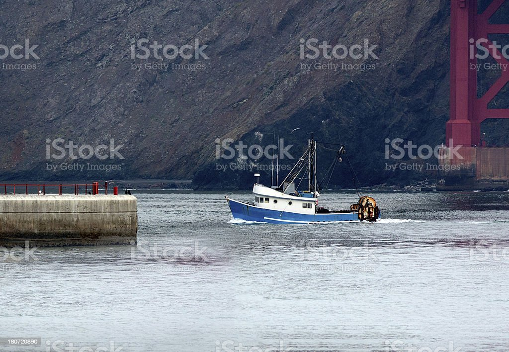 Fishing boat sails out to sea past Golden Gate bridge royalty-free stock photo