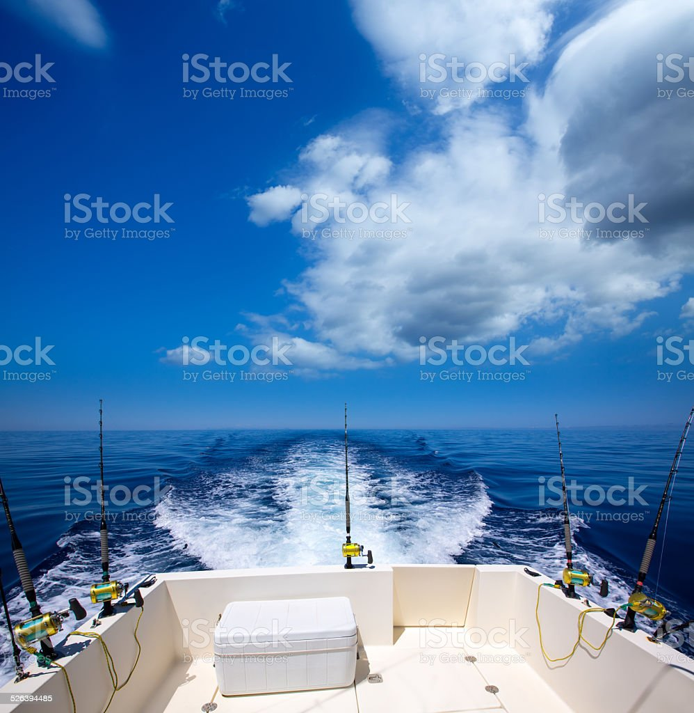 Fishing boat stern deck with trolling fishing rods and reels stock photo
