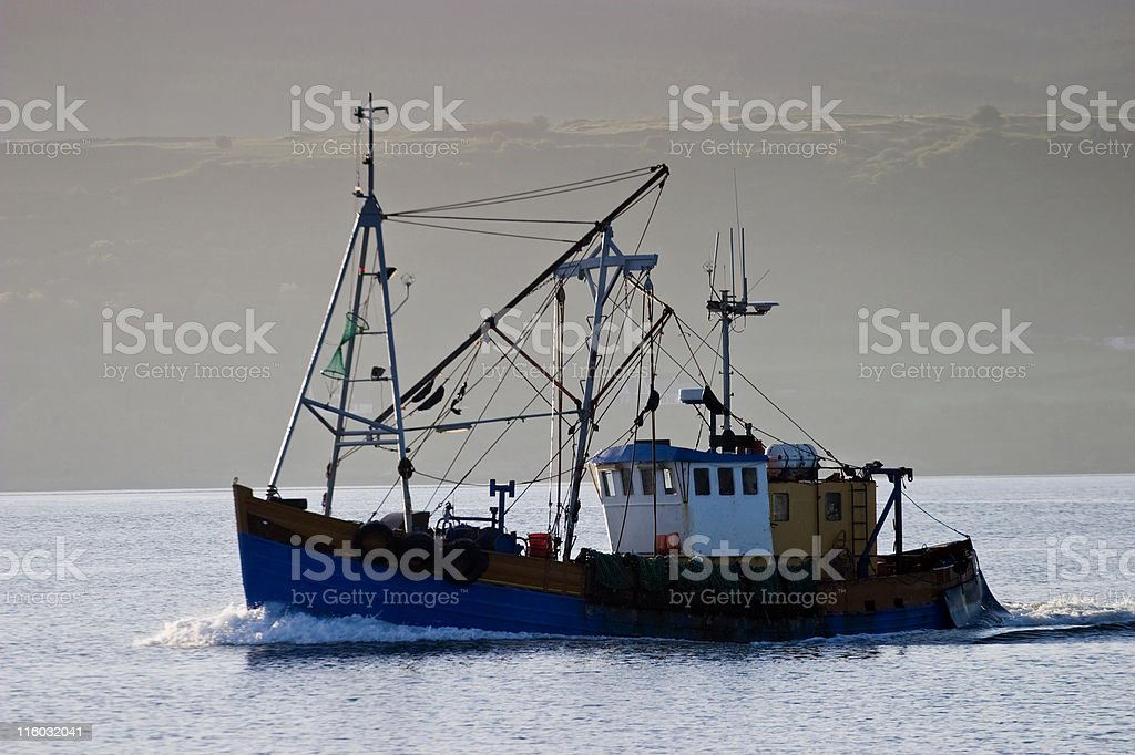 Fishing boat with shoreline in the background royalty-free stock photo