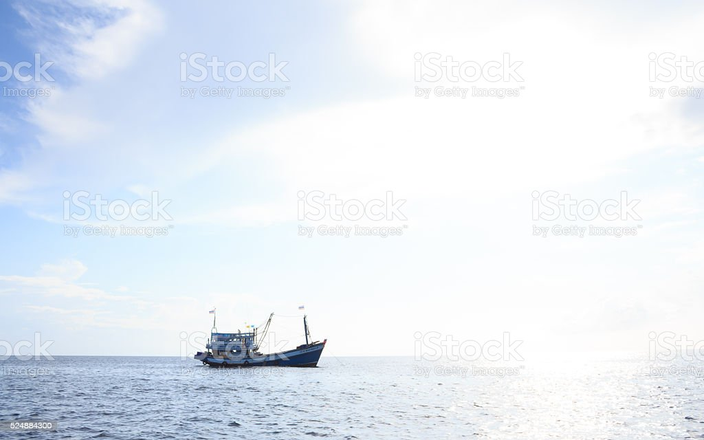 fishing boat with sunset reflect tropical clear water sea stock photo