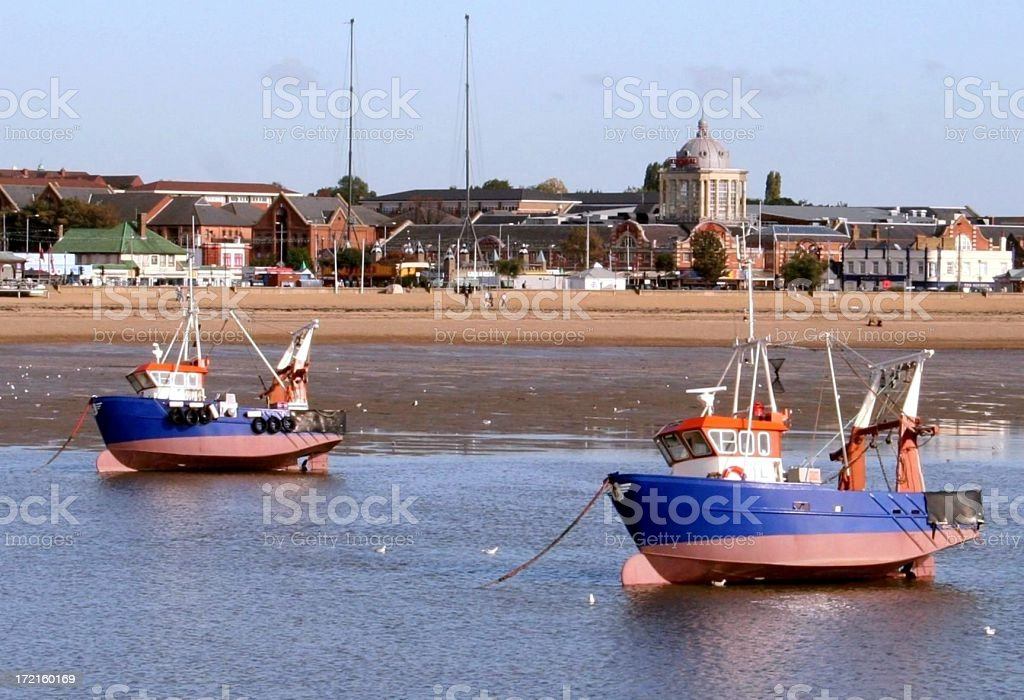 Fishing boats at low tide on a nice day stock photo