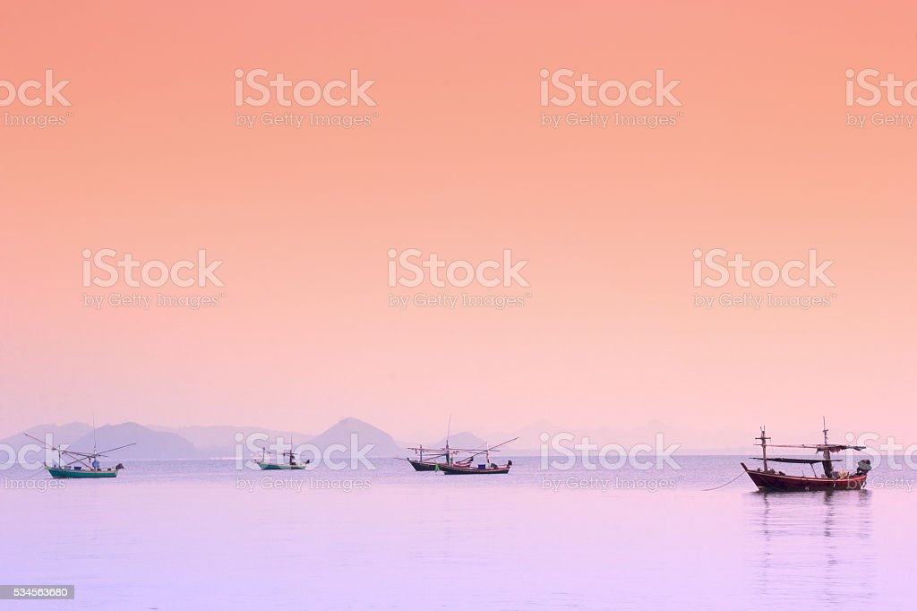 Fishing boats at sea with the morning sun. Mountain view stock photo
