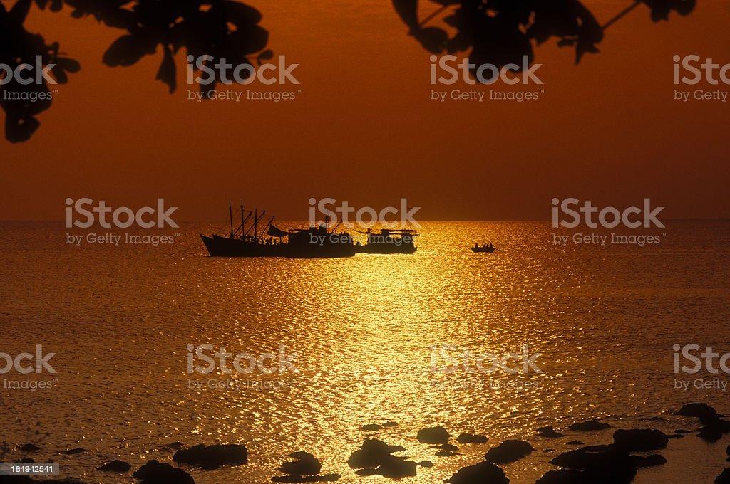Fishing boats at sunset, Halong Bay stock photo