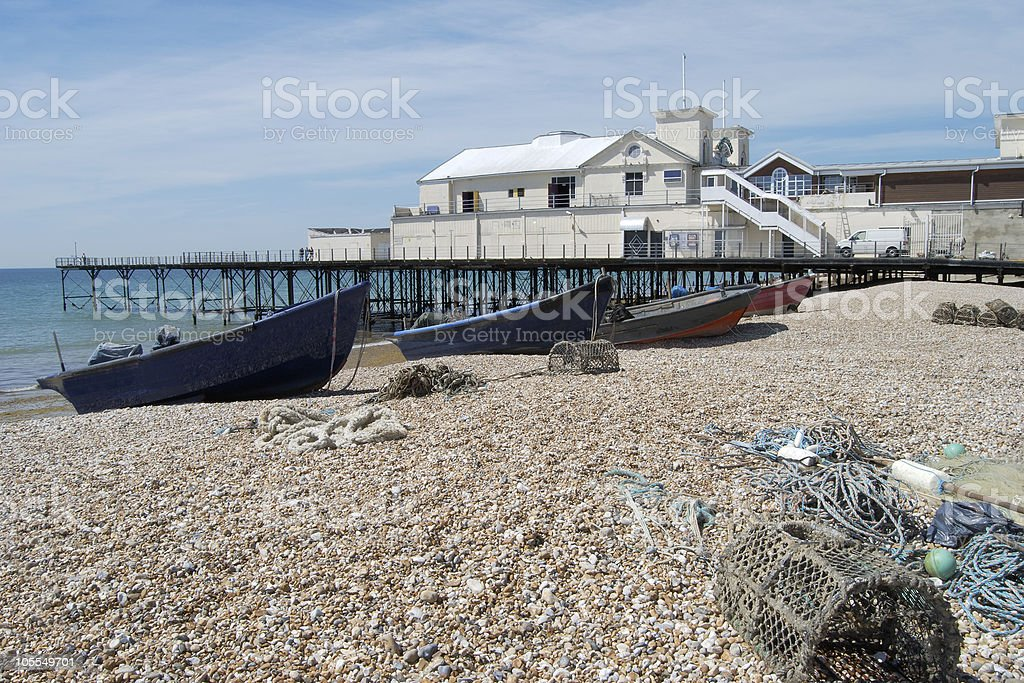Fishing boats by pier on Bognor beach. England stock photo
