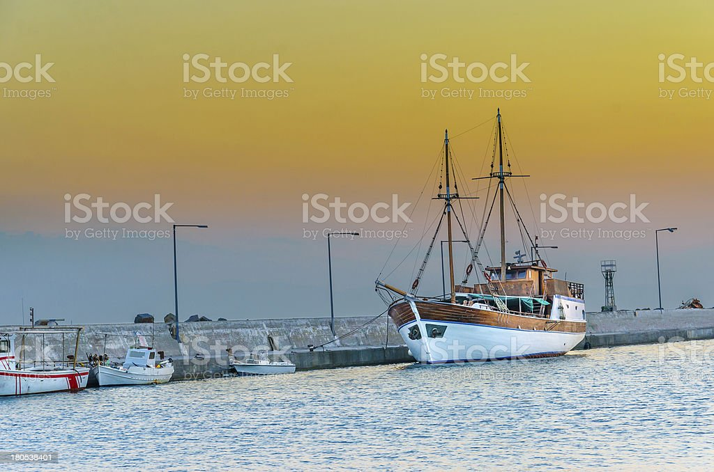 fishing boats in harbor on dramatic sunset sky stock photo
