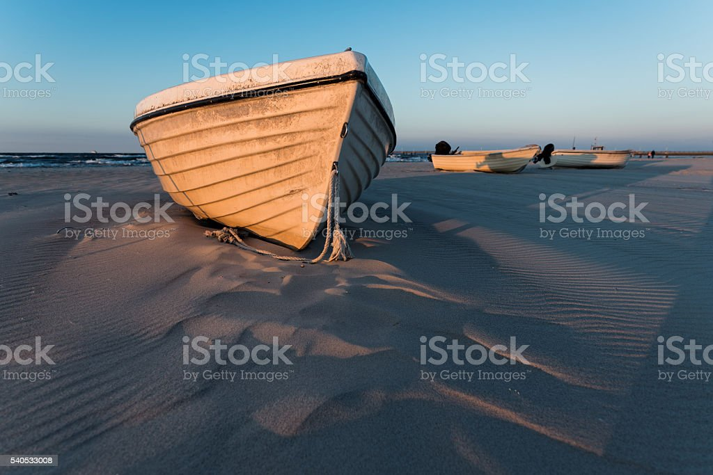Fishing Boats in sunlight on sand beach stock photo