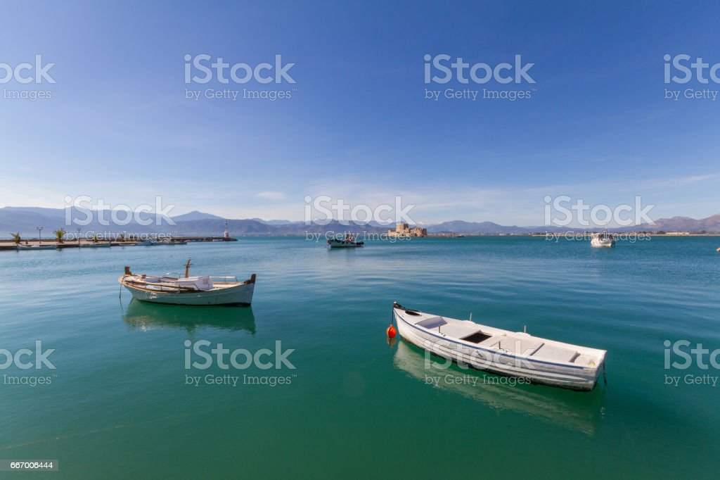 Fishing Boats, Lightouse and Bourtzi Fortress in Nafplion, Greece- wide-angle photo stock photo