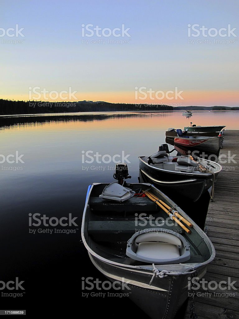 Fishing boats line dock at sunset royalty-free stock photo