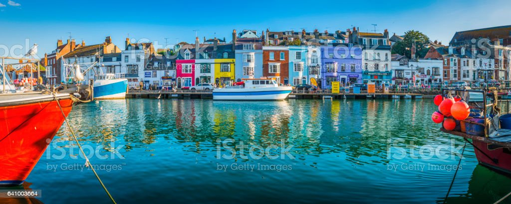 Fishing boats moored in busy harbour colourful cottages Weymouth Dorset stock photo