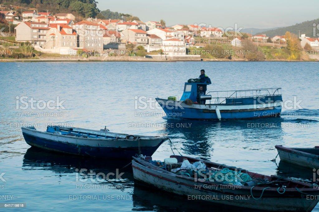 Fishing boats mooring at dusk, fisherman arriving. Galicia, Spain. stock photo