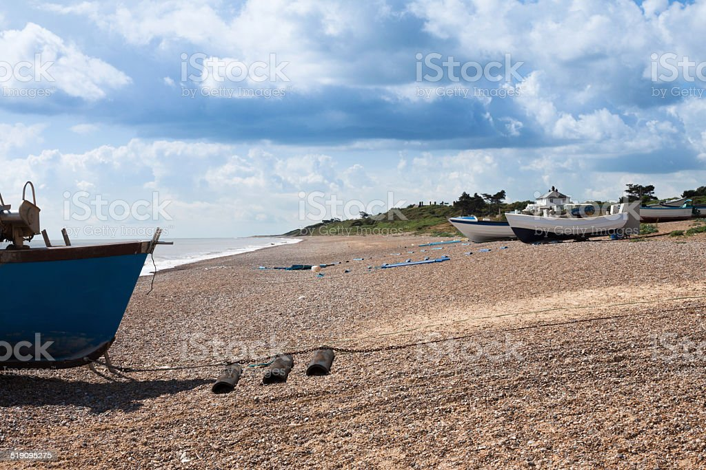 fishing boats on sunny gravel beach in Sizewell Suffolk England stock photo