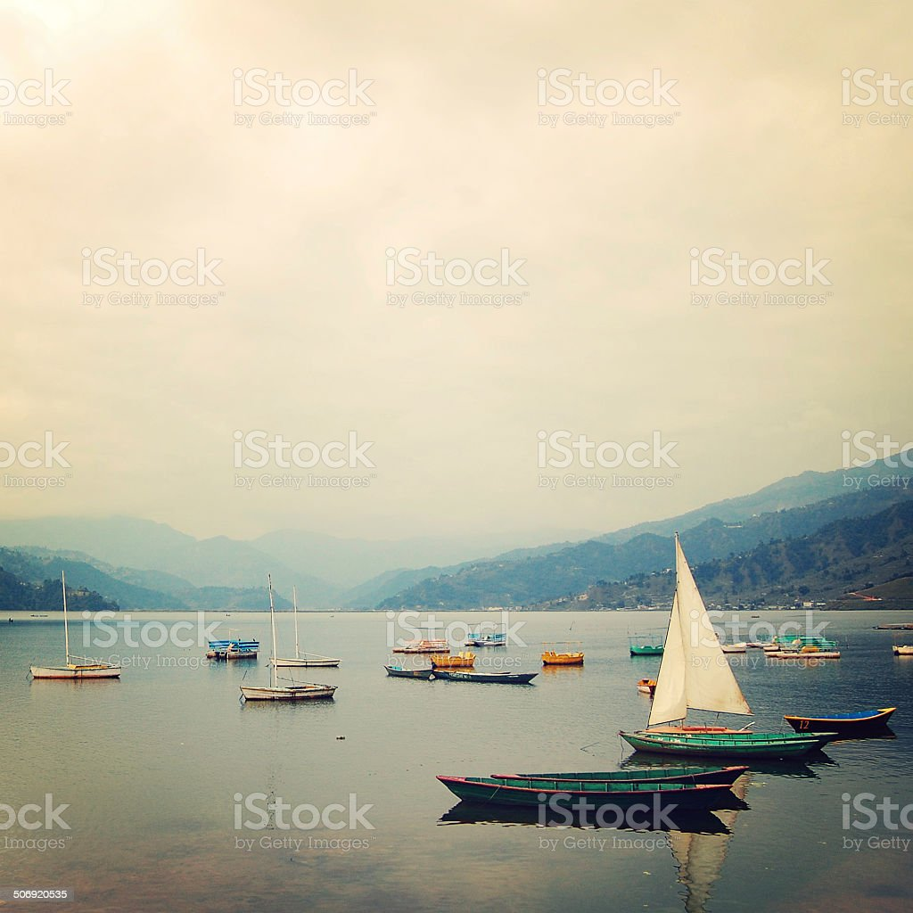 Fishing boats on the lake vintage effect. Colorful retro photo. stock photo