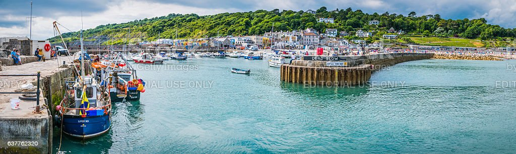 Fishing boats tourists on harbour wall Lyme Regis panorama Dorset stock photo