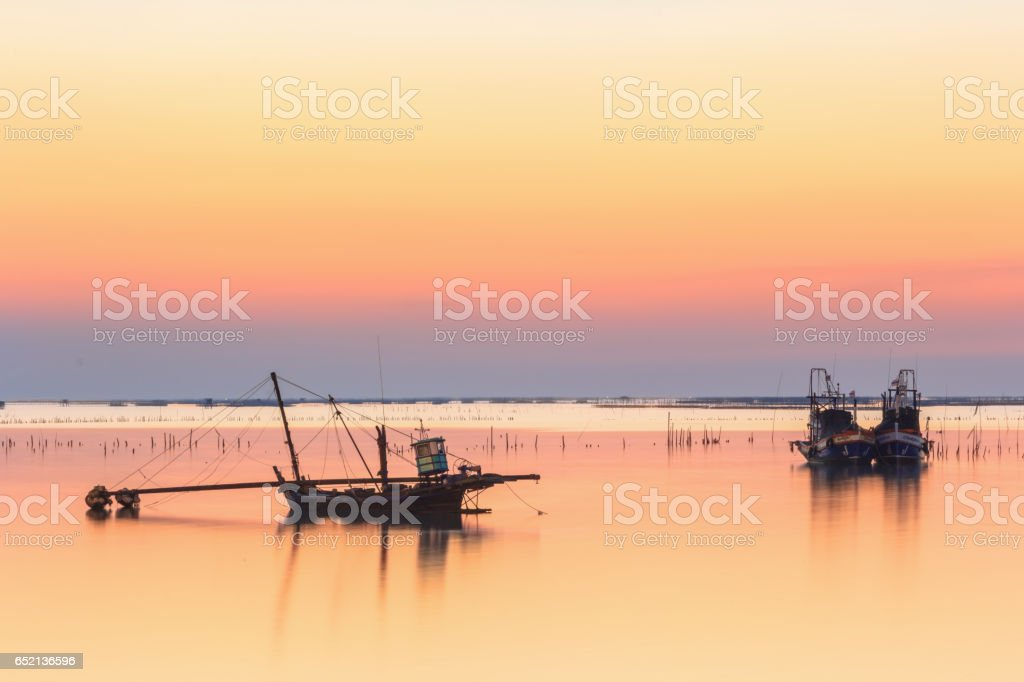 fishing boats used as a vehicle for finding fish in the sea.at sunset stock photo