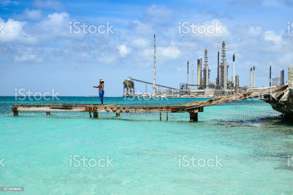 Fishing by a refinery on the Caribbean royalty-free stock photo