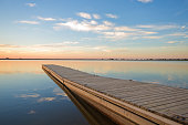 Fishing dock on a lake at sunrise with clouds