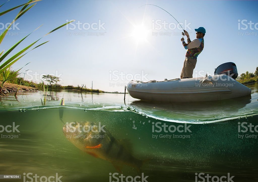 Fishing. Fisherman on the boat. Underwater view stock photo
