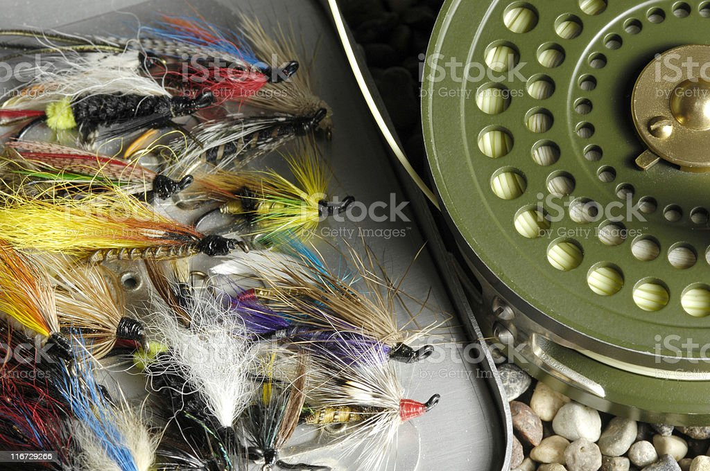 Fishing flies in fly box beside reel royalty-free stock photo