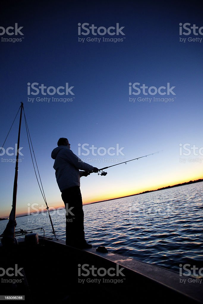 Fishing from a sailboat at sunset stock photo