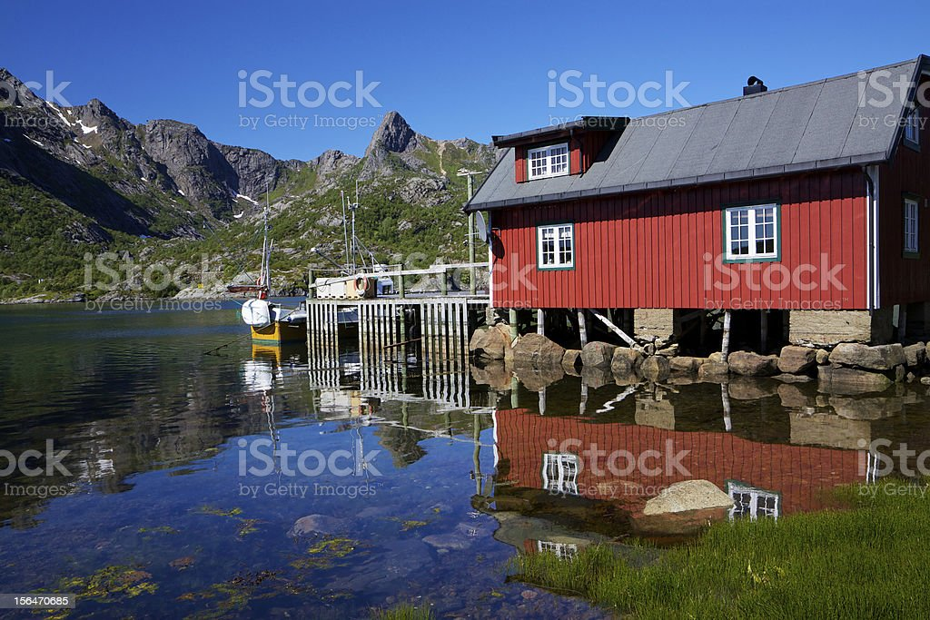 Fishing hut reflecting in fjord royalty-free stock photo