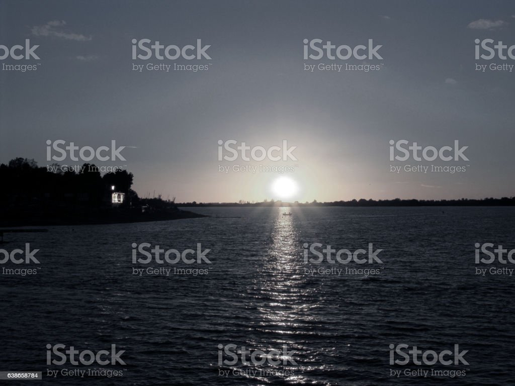 Fishing in a boat at sunset on a reservoir stock photo