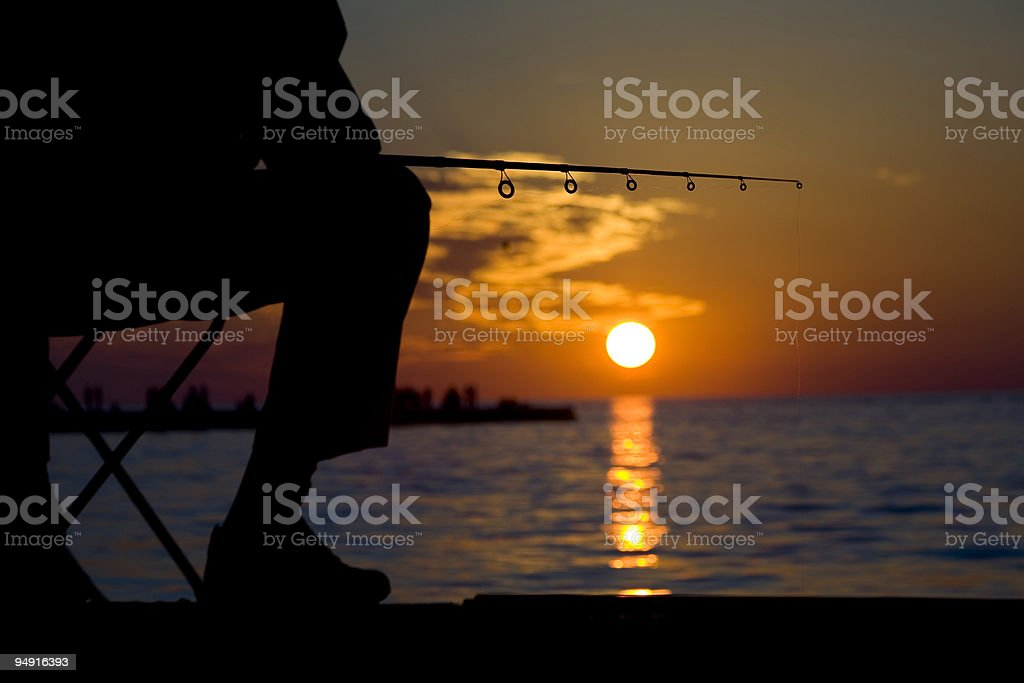 fishing in the sunset stock photo