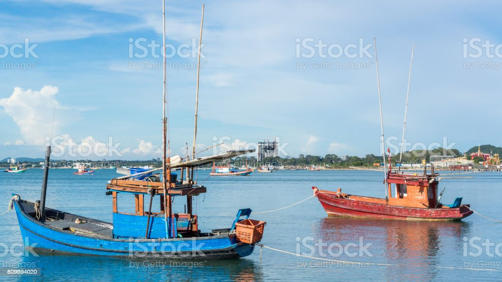 2 little fishing boats on a beach in with the city of Pattaya in...