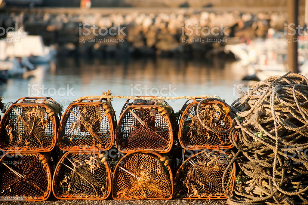 Fishing net baskets and rope on a harbor dock. stock photo