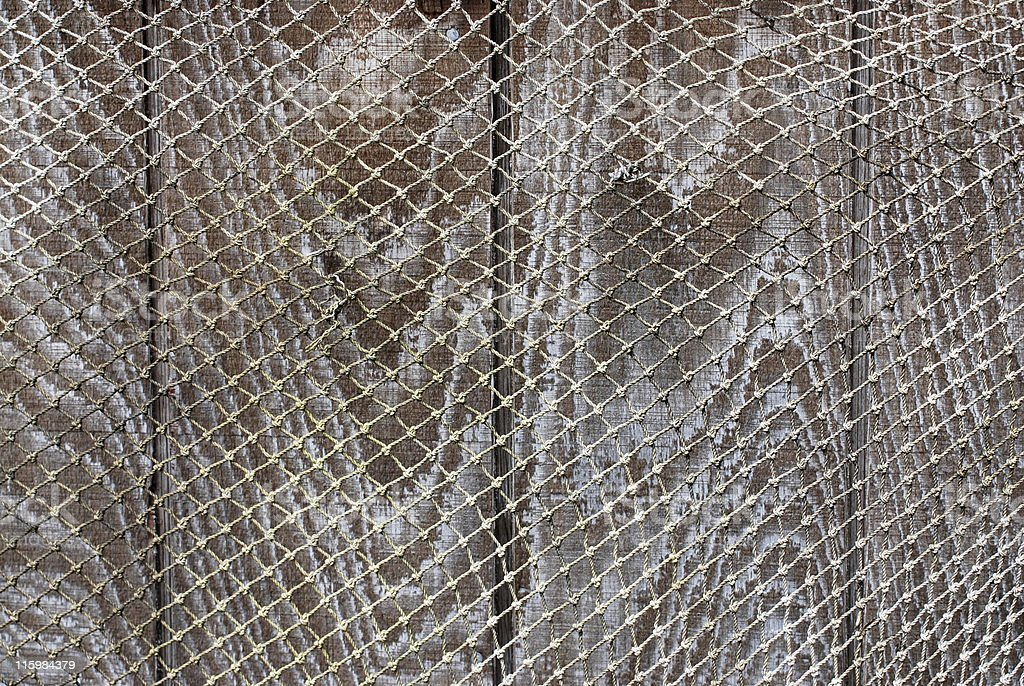 fishing net over board fence stock photo