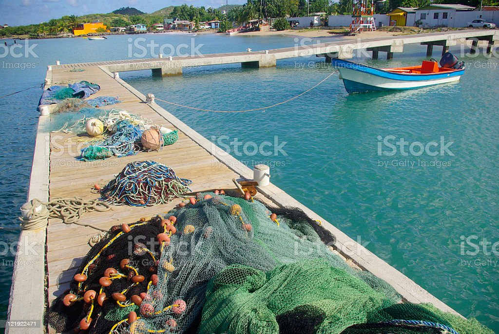 fishing nets and pier with boat on turquoise Caribbean sea stock photo