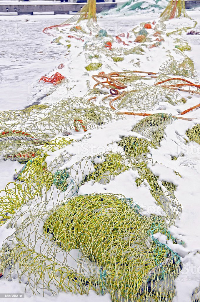 Fishing nets in snow on commericial docks stock photo