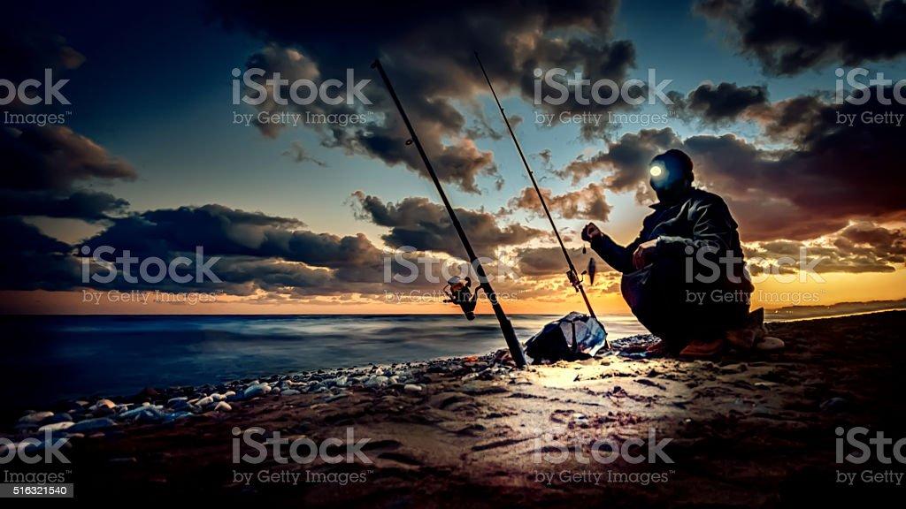 Fishing on coast at sunset time stock photo