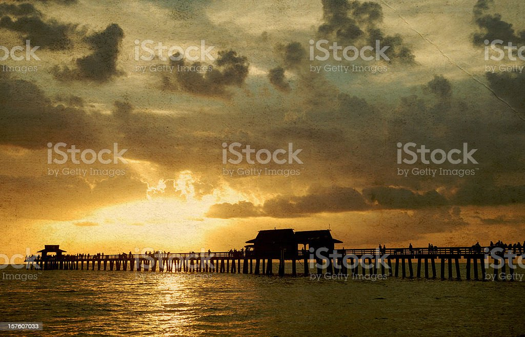 Fishing pier at sunset on grunge post card stock photo