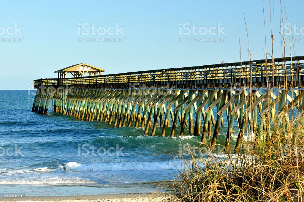 Fishing pier reaching out into ocean. stock photo