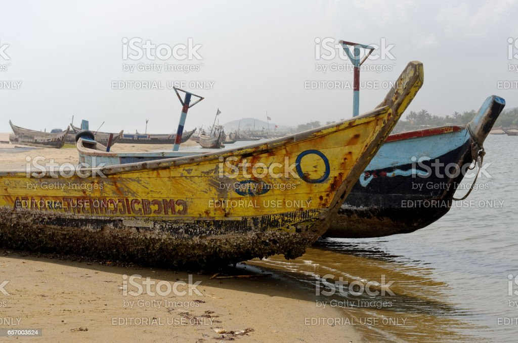 ACCARA, GHANA - FEBRUARY 22, 2014: Fishing poor boats on sea sand coast in rural fishing village.  In 1957, Ghana became the first African nation to declare independence from European colonization. stock photo