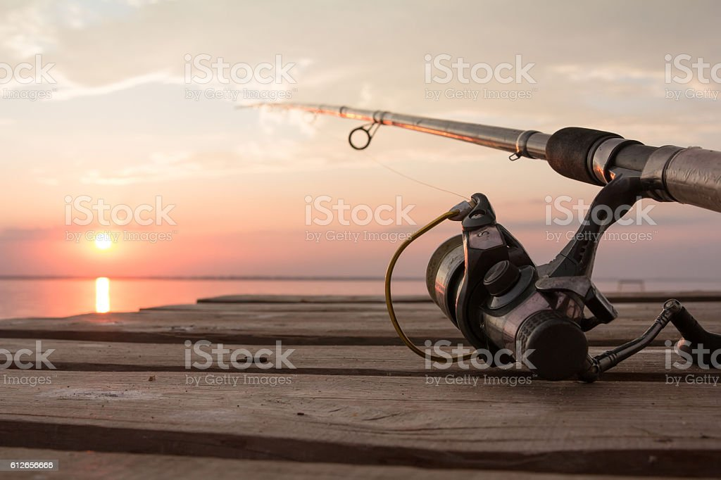 Fishing reel and rod lying on wooden pier over the stock photo
