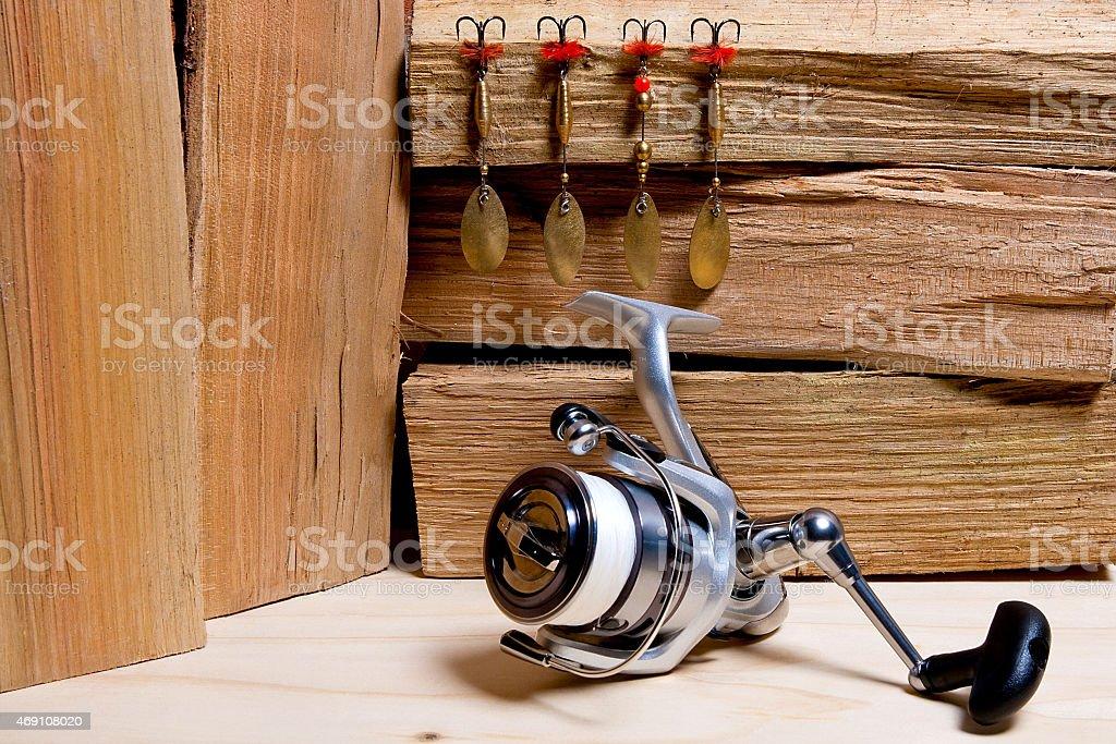 Carrete de pesca con baits de metal sobre fondo de madera. foto de stock libre de derechos