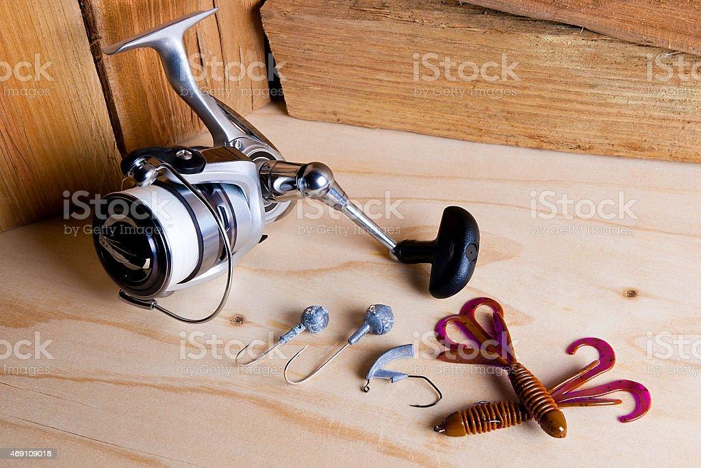 Carrete de pesca con silicona baits sobre fondo de madera. foto de stock libre de derechos