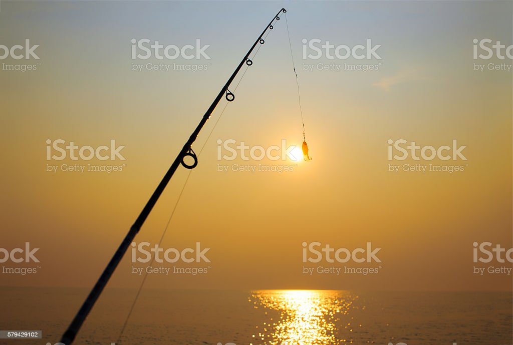 fishing rod and jig on background of the setting sun stock photo