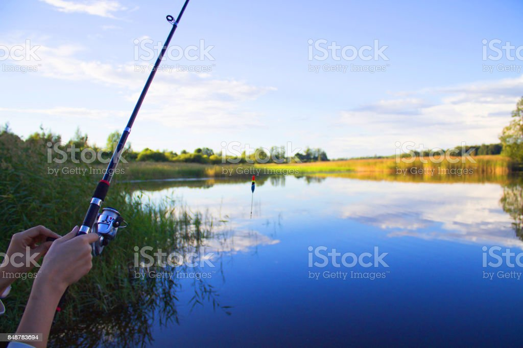 Fishing rod in hand on a background of lake stock photo