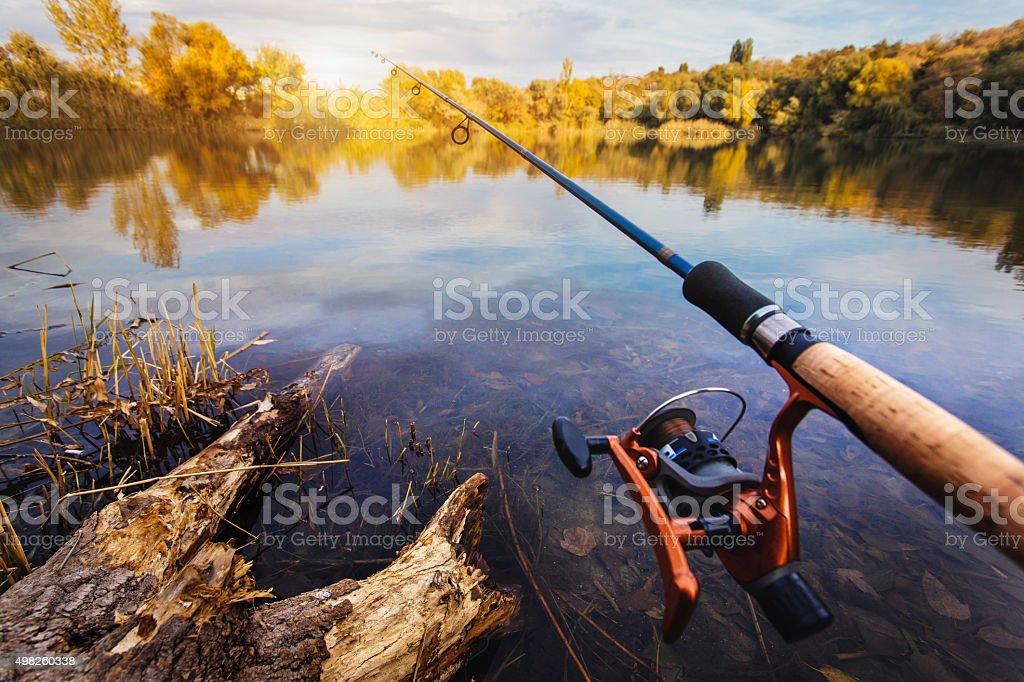 Fishing rod near beautiful pond stock photo
