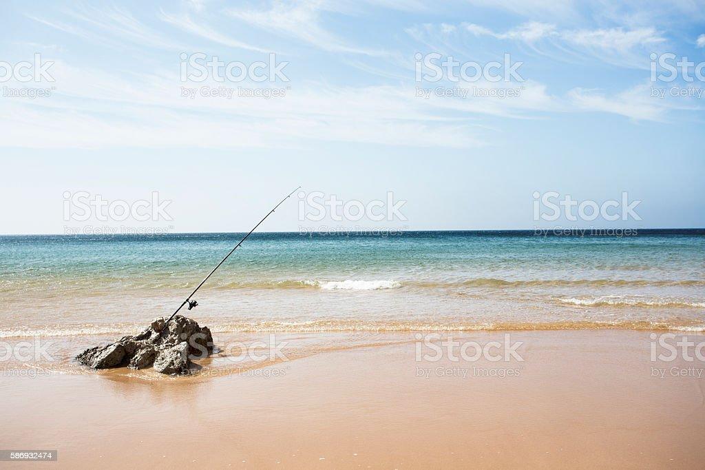 caña de pescar en la arena de la playa stock photo