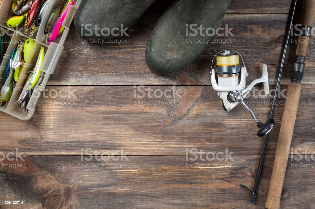 Fishing rods and reel with boots and fishing tackles in a box on wooden background with free space stock photo