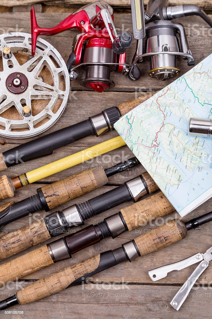 fishing rods and reels on wooden boards stock photo