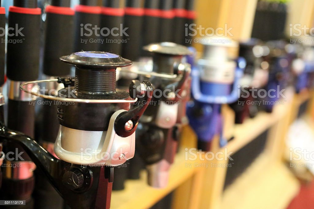 Fishing rods in a row on the shelf stock photo