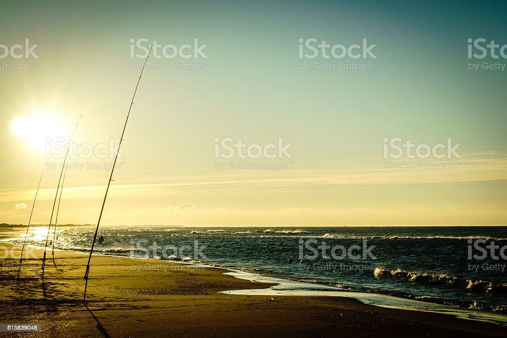 Fishing rods lining the beach stock photo