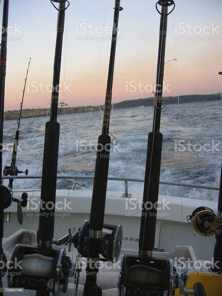 Fishing rods on a boat heading out to sea royalty-free stock photo