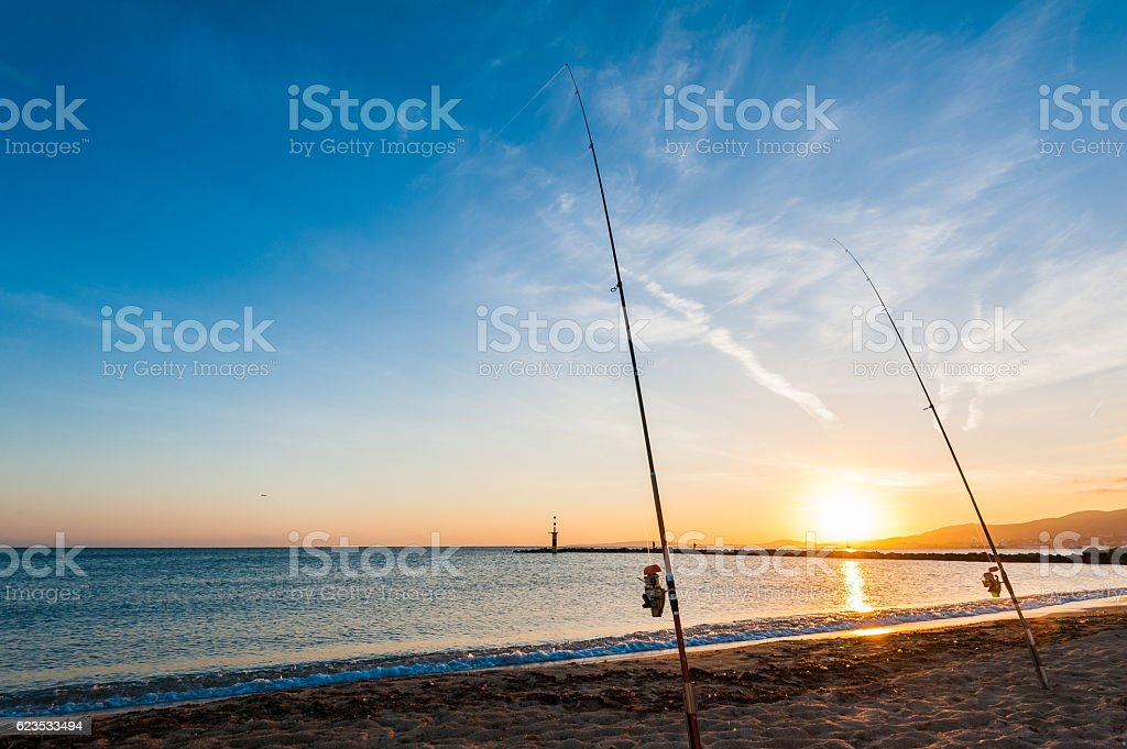 Fishing rods on sand at sunset stock photo