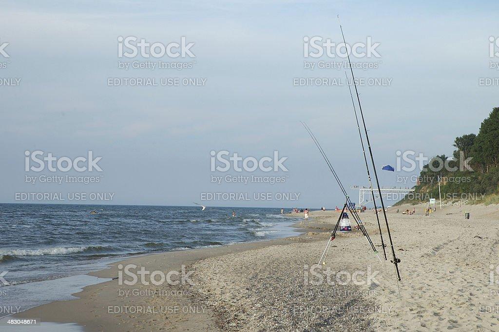Fishing rods on sandy beach stock photo