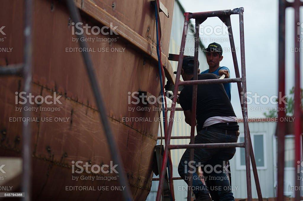 Fishing ship building yard workers stock photo